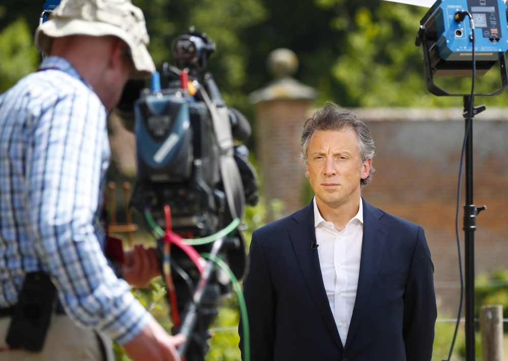 Tom Newton Dunn, political editor of the Sun Newspaper, right, waits to speak to Fox Television News network at Chequers, in Buckinghamshire, England, Friday, July 13, 2018. In an interview with Sun newspaper, President Trump slammed British Prime Minister Theresa May's plan for British departure from the Europe Union and praised her political rival Boris Johnson, who quit May's Cabinet this week over Brexit differences. (Pablo Martinez Monsivais/AP)