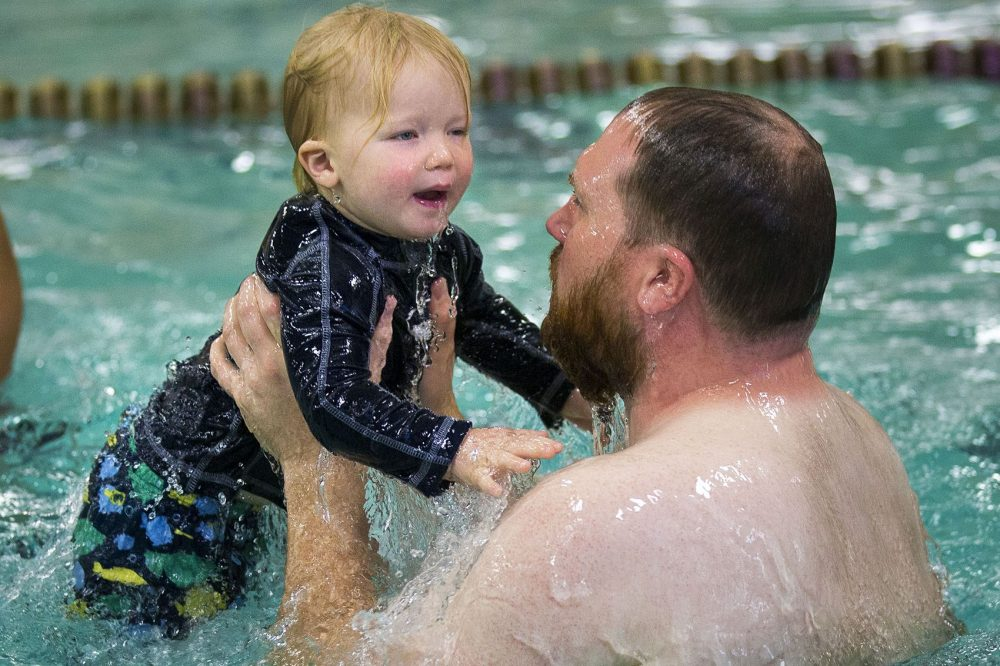 Twenty-three-month-old Ferdinand Smith and his father Nate come up from the water after dunking themselves during a game of Ring Around the Rosie during a toddler swimming lesson at the YMCA in Waltham. (Jesse Costa/WBUR)