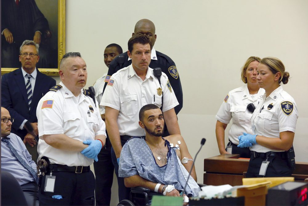 Court officers surround Emanuel Lopes during his arraignment Tuesday in district court in Quincy, Mass. (Greg Derr/The Quincy Patriot Ledger via AP, pool)