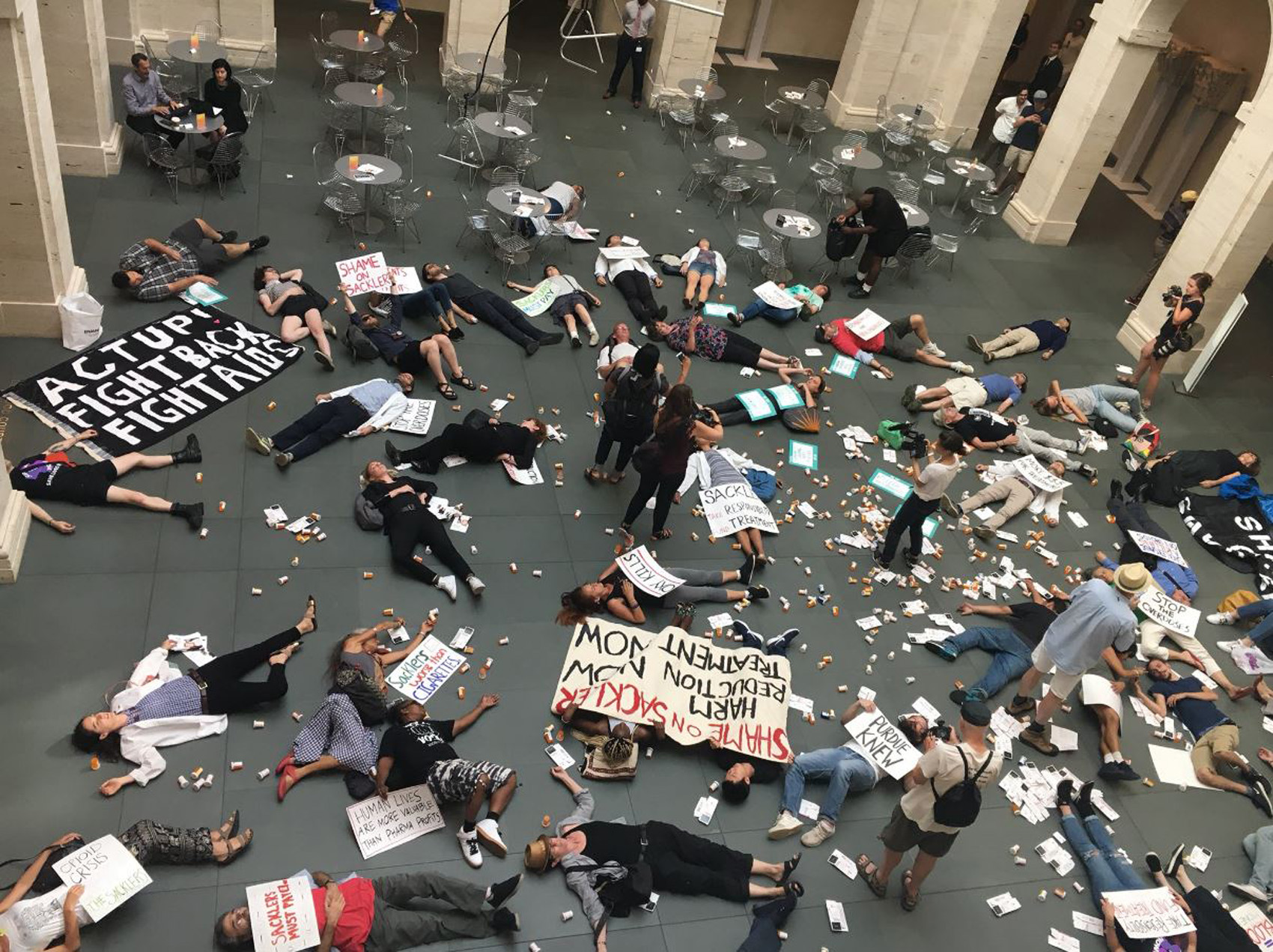 """Protesters stage a """"die-in"""" inside Harvard's Arthur M. Sackler Museum to protest the Sackler family's ties to Purdue Pharma and the opioid crisis. (Justin Kaplan/WBUR)"""