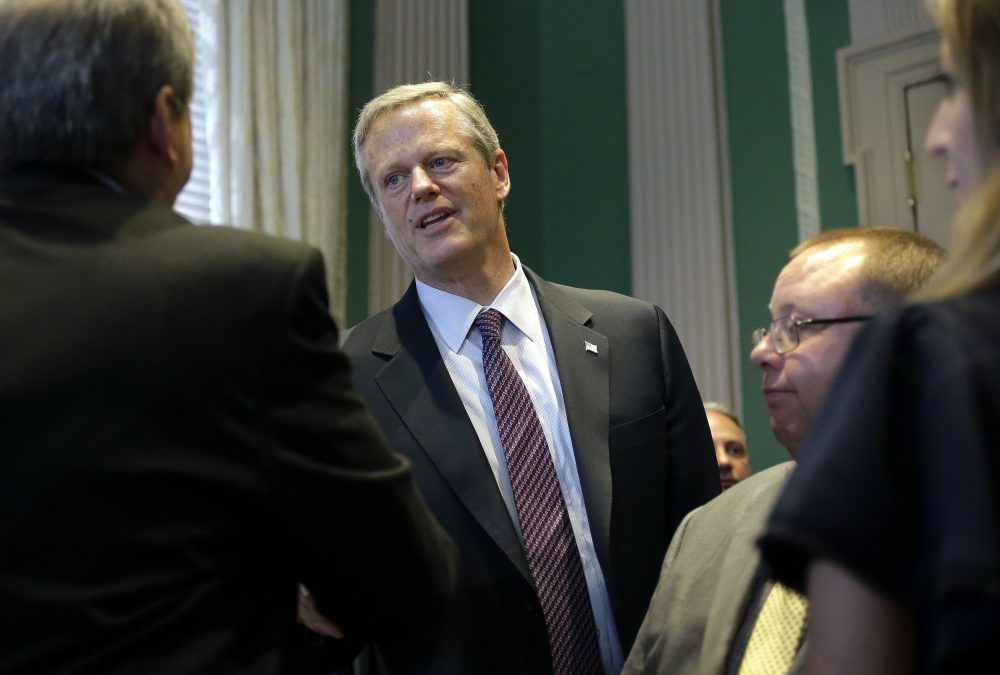 Republican Gov. Charlie Baker, center, shakes hands at the conclusion of a bill signing ceremony Wednesday at the State House in Boston. (Steven Senne/AP)