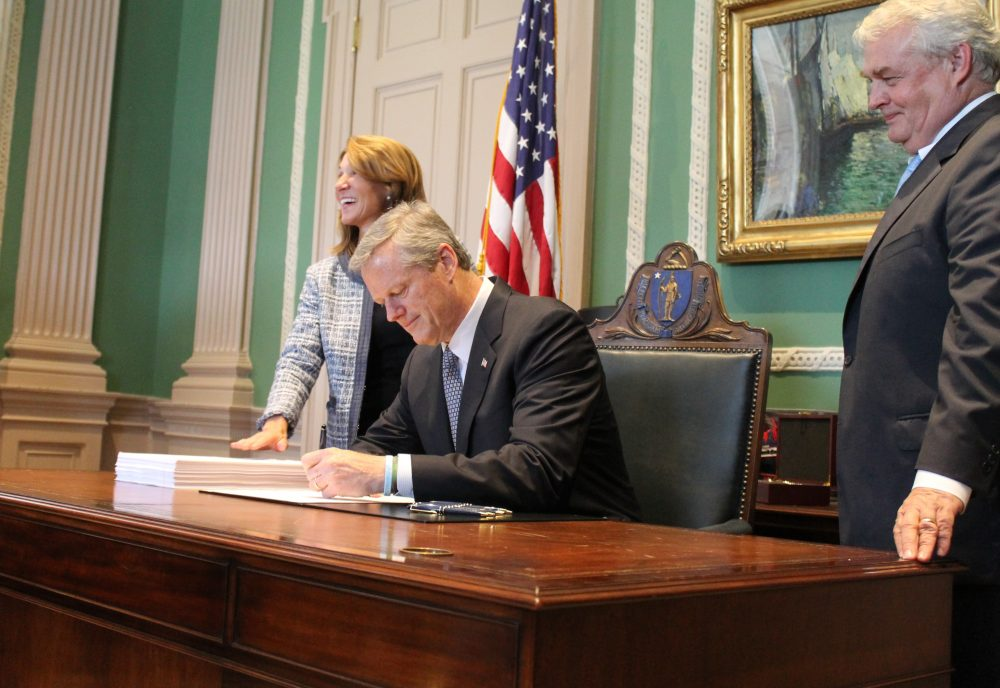 Gov. Charlie Baker signed the fiscal 2019 budget in his office alongside Lt. Gov. Karyn Polito and Administration and Finance Secretary Mike Heffernan. (Sam Doran/State House News Service)