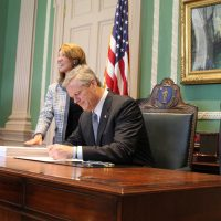 Gov. Charlie Baker signed the fiscal 2019 budget in his office alongside Lt. Gov. Karyn Polito and Administration and Finance Secretary Mike Heffernan in July 2018. (Sam Doran/State House News Service)