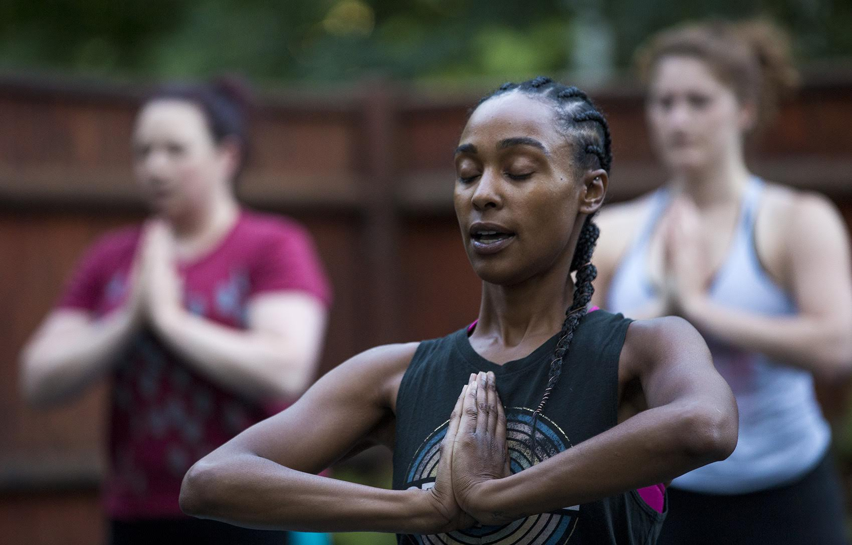 Kijana Rose directs her Beginners Ganja Yoga Flow students. (Jesse Costa/WBUR)
