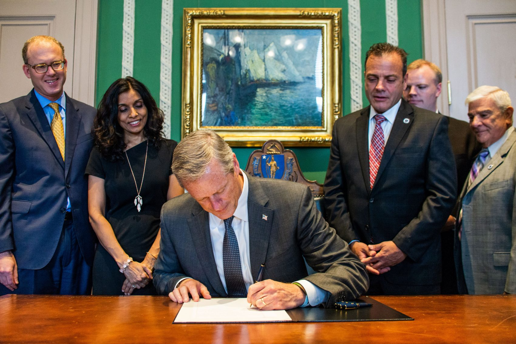 Gov. Charlie Baker signs into law a statewide measure that raises the legal age to purchase tobacco products from 18 to 21. (Courtesy Josephine Pettigrew/Office of the Governor via flickr)