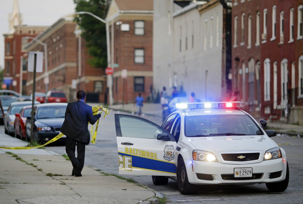 In this July 30, 2015 picture, a member of the Baltimore Police Department removes crime scene tape from a corner where a victim of a shooting was discovered in Baltimore. (Patrick Semansky/AP)
