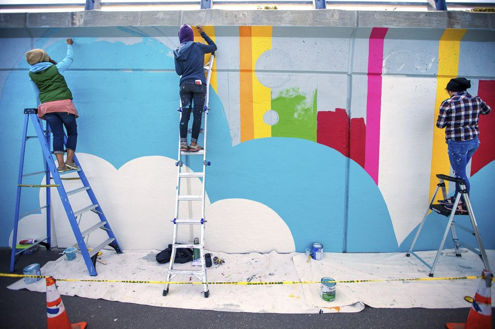 Artists work on a mural in Boston's Kenmore Square last summer. (Jesse Costa/WBUR)
