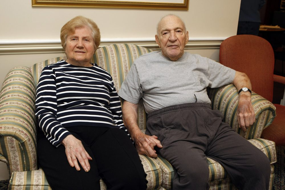 Jeannette Zeltzer, 81 and her new boyfriend Max Rakov, 92, hold hands while sitting on a couch at the assisted living facility where they live in Newton, Mass.  Rakov  suffers from Alzheimer's. (Greg M. Cooper/AP)
