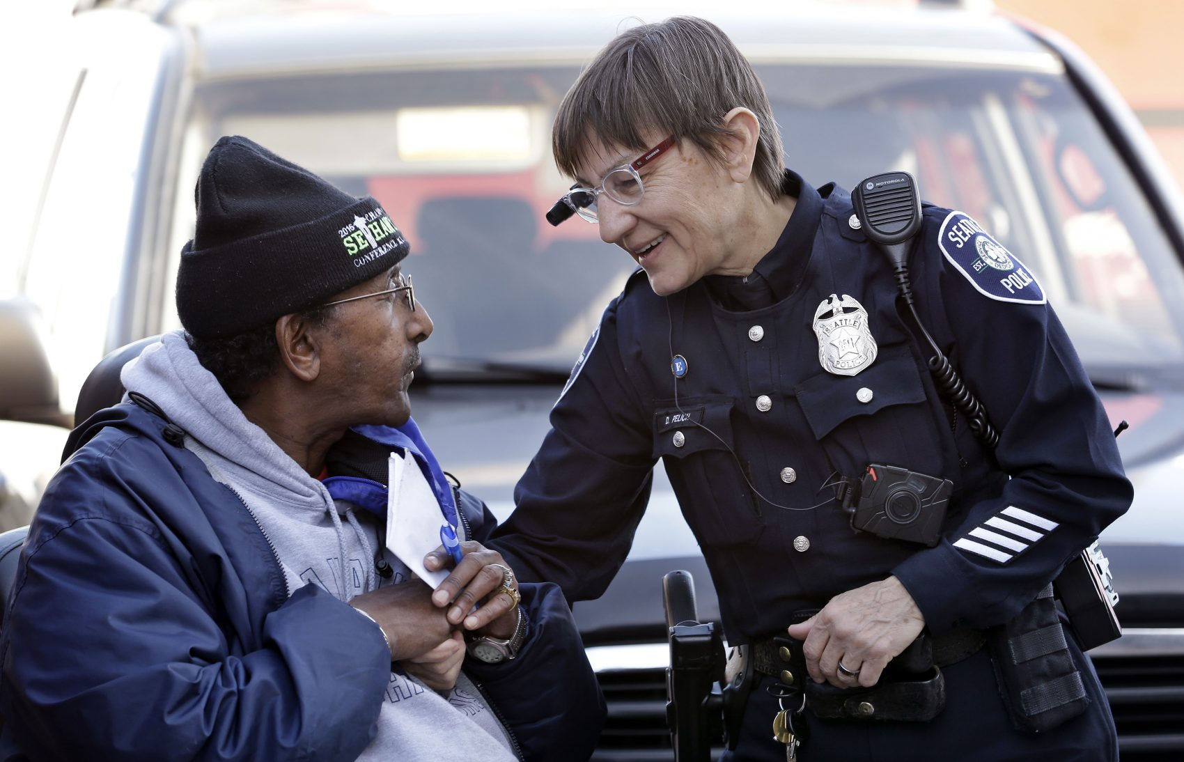 In this March 12, 2015, file photo, Seattle police officer Debra Pelich, right, wears a video camera on her eyeglasses as she talks with Alex Legesse before a small community gathering in Seattle. While the Seattle Police Department bars officers from using real-time facial recognition in body camera video, privacy activists are concerned that a proliferation of the technology could turn the cameras into tools of mass surveillance. The ACLU and other organizations on Tuesday, May 22, 2018, asked Amazon to stop selling its facial-recognition tool, called Rekognition, to law enforcement agencies. (Elaine Thompson/AP)