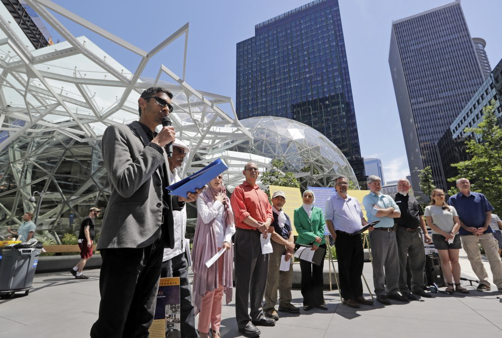 Shankar Narayan, legislative director of the ACLU of Washington, left, speaks at a June 18 news conference outside Amazon headquarters in Seattle. Community-based organizations urged Amazon to stop selling its face surveillance system, Rekognition, to the government. (Elaine Thompson/AP)