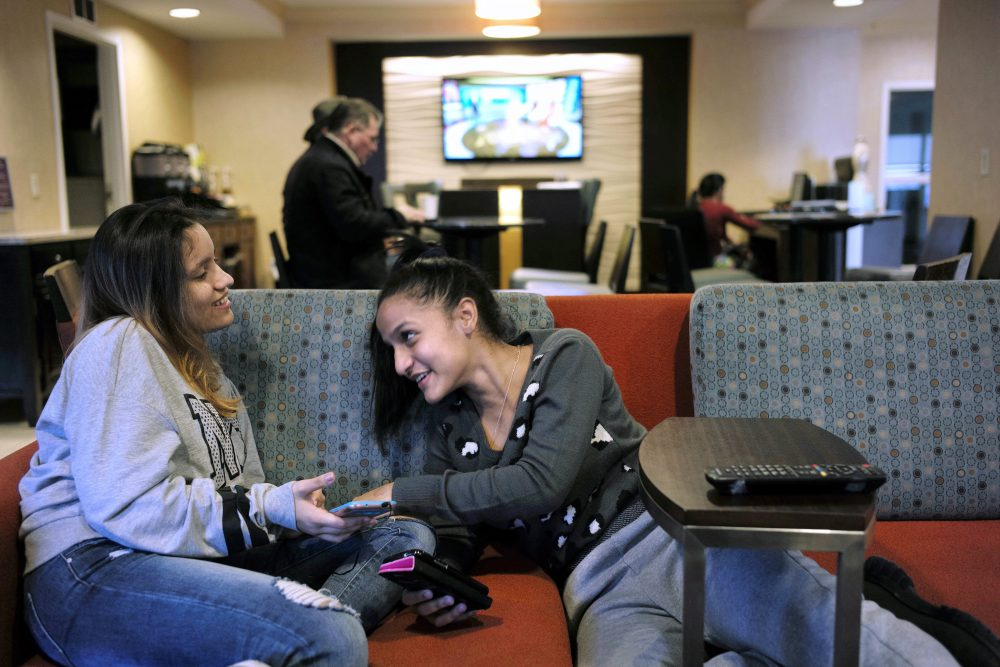 In this Feb. 27 file photo, 15-year-old Alanis Rodriguez, left, of Canovanos, Puerto Rico, and 14-year-old Bethel Sanchez, right, of Isabela, Puerto Rico, spend time together in a hotel lobby in Dedham, where they lived temporarily after Hurricane Maria hit the island in September. (Steven Senne/AP)