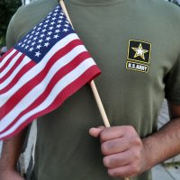 In this Tuesday, July 3, 2018 photo, a Pakistani recruit, 22, who was recently discharged from the U.S. Army, holds an American flag as he poses for a picture. The man asked his name and location to be undisclosed for safety reasons. The AP interviewed three recruits from Brazil, Pakistan and Iran, all of whom said they were devastated by their unexpected discharges. (Mike Knaak/AP)