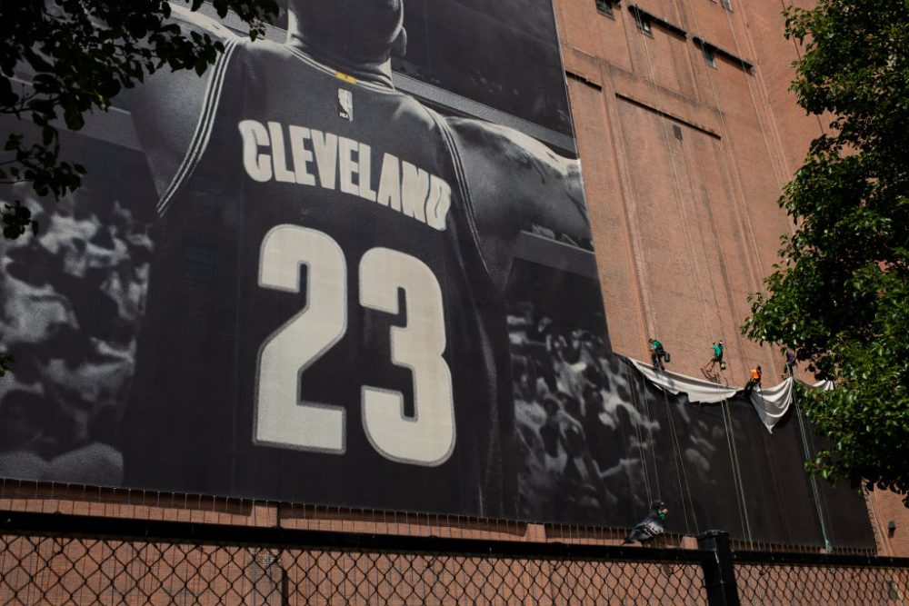 Workers take down the LeBron James banner from Cleveland's Sherwin Williams building. James is on his way to Los Angeles. (Angelo Merendino/Getty Images)