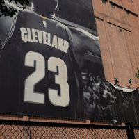 Workers take down the LeBron James banner from Cleveland's Sherwin Williams building. James is on his way to Los Angeles. (Photo by Angelo Merendino/Getty Images)