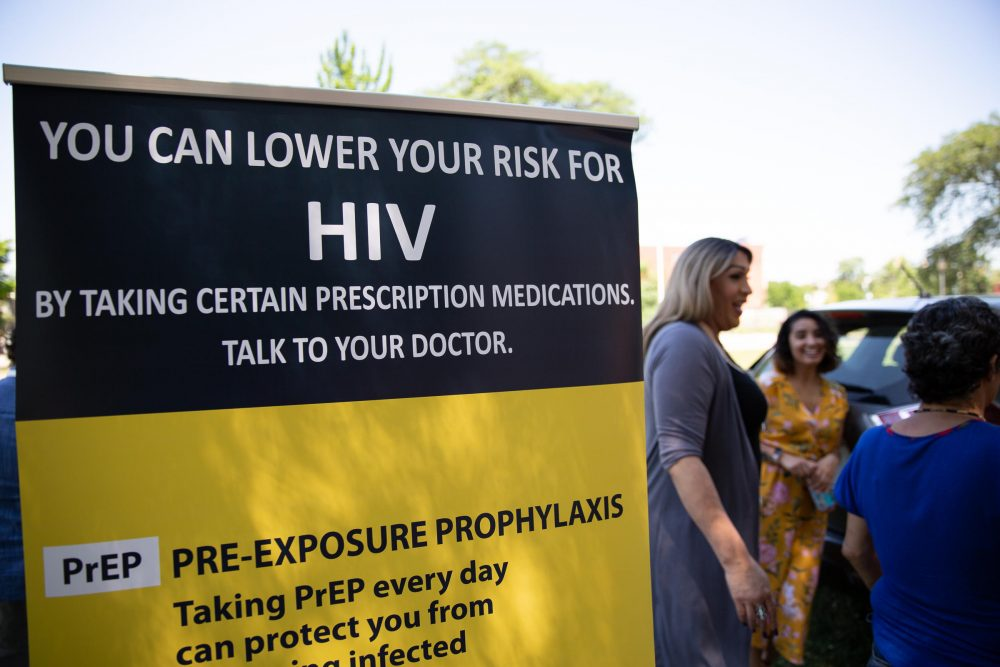 Tatiana Melendez, standing tall next to the PrEP promotional poster, does HIV prevention outreach at Hartford's Barnard Park on a recent Friday. (Ryan Caron King/NENC)