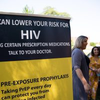 Tatiana Melendez, standing tall next to the PrEP promotional poster, does HIV prevention outreach at Hartford's Barnard Park. (Ryan Caron King/NENC)