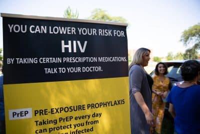 Tatiana Melendez, standing tall next to the PrEP promotional poster, does HIV prevention outreach at Hartford's Barnard Park. (Ryan Caron King/NENC)