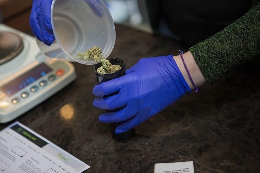 Patient Service Associate Ashley Cabana dispenses 14 grams (1/2 oz) of Facewreck marijuana flower for patient Sam Brown. (Jesse Costa/WBUR)