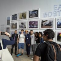 Visitors to the inaugural exhibition of the ICA Watershed pose for a photo in front of a wall of photographs of East Boston by teens from the ICA's digital photography program, June 2018. (Robin Lubbock/WBUR)