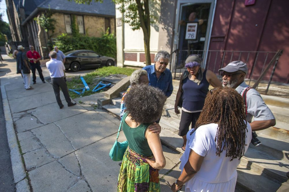 Members of the African-American Master Artists-in-Residence Program (AAMARP) gather outside the 76 Atherton St. warehouse after Northeastern University's original notice to vacate. (Jesse Costa/WBUR)