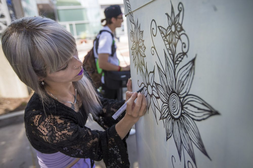 Artist Kitty Zen drawing a design on an electrical box on the corner of Massachusetts Ave and Melnea Cass Boulevard, July 2017. (Jesse Costa/WBUR)