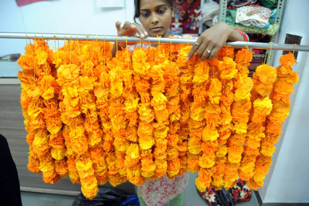 An Indian employee arranges floral garlands made from fabric for a wedding decoration. (Sam Panthaky/AFP/Getty Images)