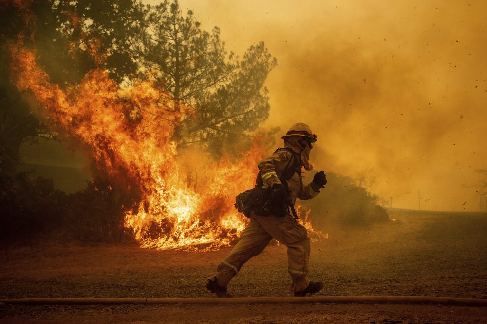 A firefighter runs while trying to save a home as a wildfire tears through Lakeport, Calif., Tuesday, July 31, 2018. (Noah Berger/AP)