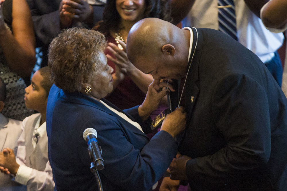 Gross bows his head to receive his new Boston police commissioner badge from his mother Deanna. (Jesse Costa/WBUR)