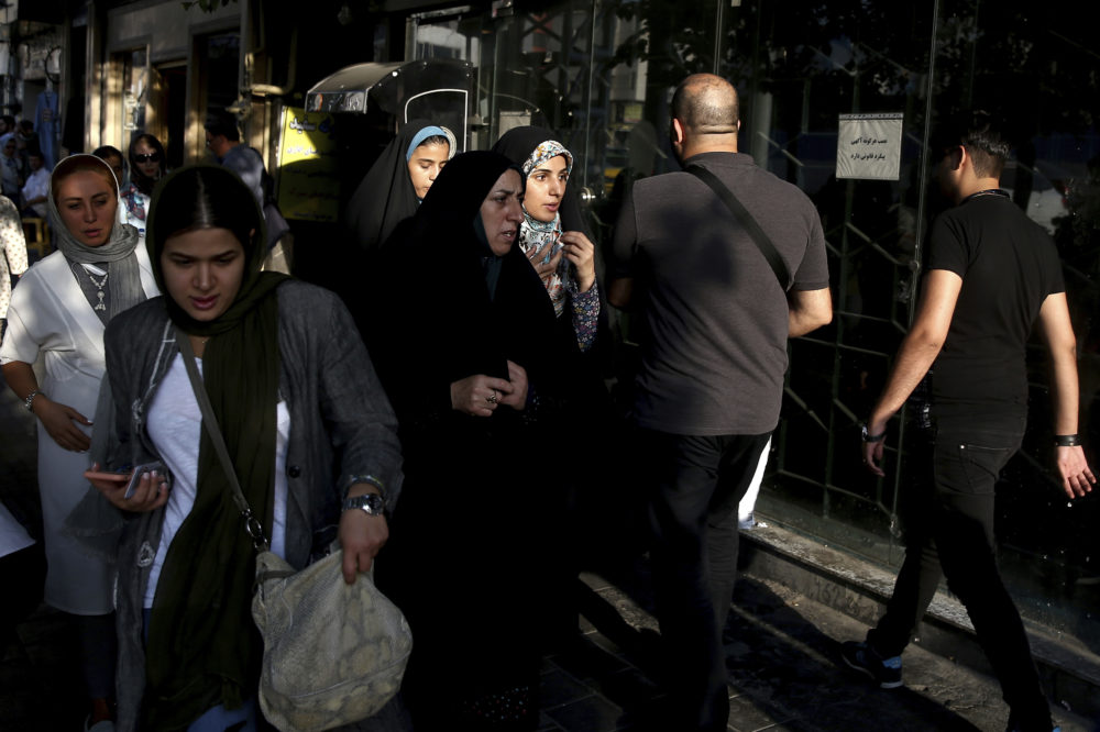 People make their way on a sidewalk in downtown Tehran, Iran, Monday, July 30, 2018. Iran's currency has dropped to a record low ahead of the imposition of renewed American sanctions, with many fearing prolonged economic suffering or possible civil unrest. (Ebrahim Noroozi/AP)