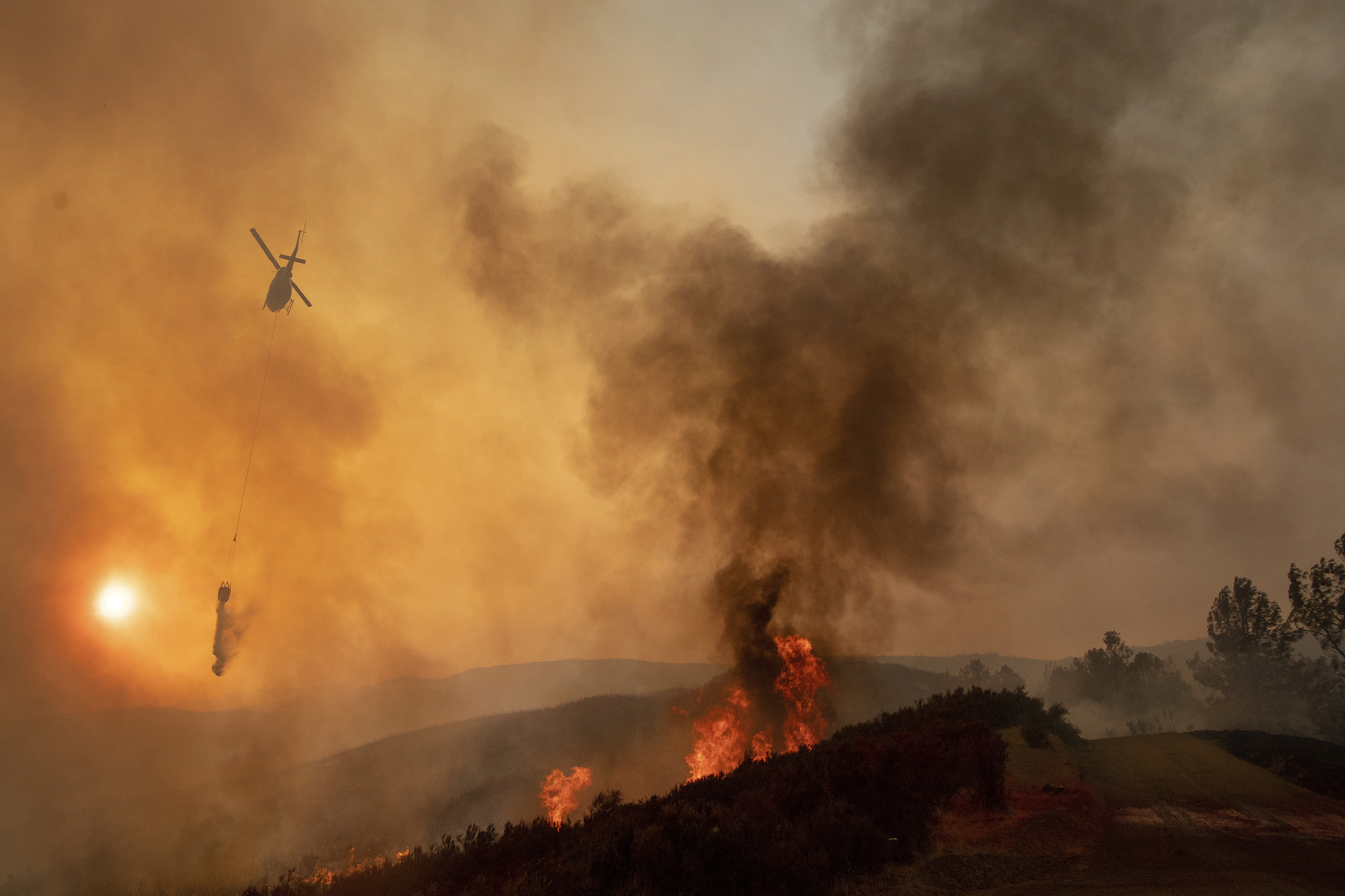 In this Sunday, Aug. 5, 2018, file photo, a helicopter drops water on a burning hillside during the Ranch Fire in Clearlake Oaks, Calif. Authorities say a rapidly expanding Northern California wildfire burning over an area the size of Los Angeles has become the state's largest blaze in recorded history. It's the second year in a row that California has recorded the state's largest wildfire. (Josh Edelson, File/AP)