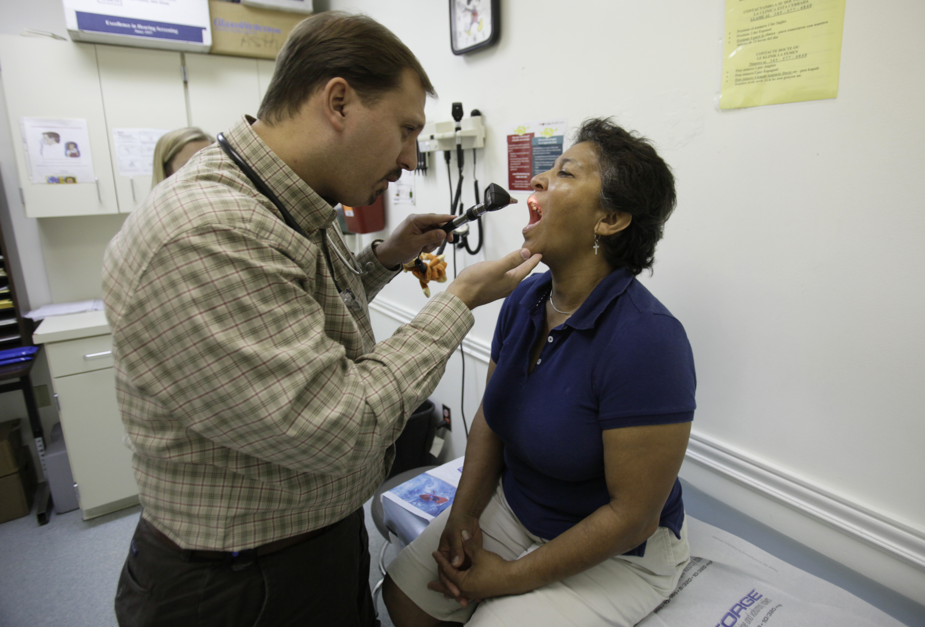 Dr. Javier Hiriart, left, examines a patient during a medical checkup at Camillus Health Concern in Miami on Sept. 8, 2009.(Lynne Sladky/AP)
