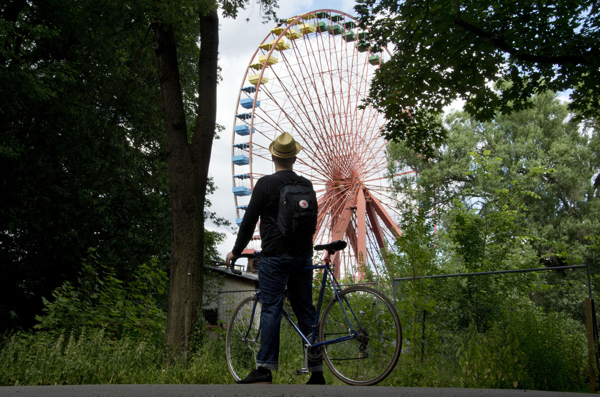A man looks at a Ferris wheel in Berlin as he stands with his bicycle outside the fence of the former amusement park Spreepark. (Odd Andersen/AFP/Getty Images)