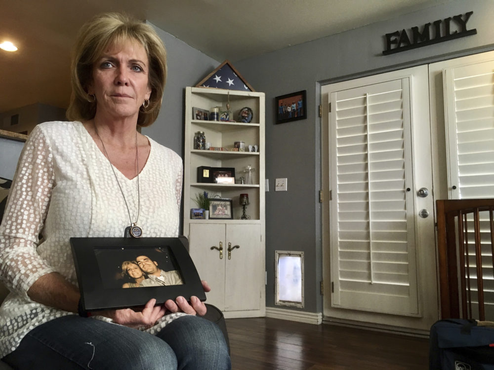 Mary Ann Mendoza poses for a photograph while holding a framed picture of herself and her son, Brandon Mendoza, on Thursday, March 2, 2017, at her home in Mesa, Ariz. Mendoza's son, a Mesa police officer, was killed on May 12, 2014, in a head-on collision with a man who authorities say was intoxicated and an immigrant in the country illegally. Both Brandon Mendoza and the other diver were killed in the crash. (Brian Skoloff/AP)