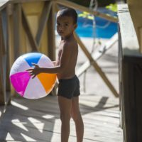 Six-year-old Hector Galvez carries a beach ball on his way to the pool in La Ceiba, Honduras. (Jesse Costa/WBUR)