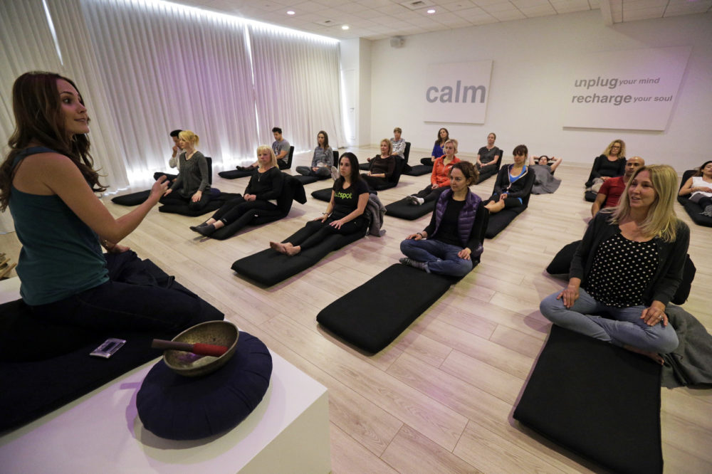 In this Feb. 21, 2016 photo, Lauren Eckstrom, left, begins a session at Unplug Meditation Center in Los Angeles. As a distracted, multi-tasking lifestyle has given way to a more self-aware, live in the moment attitude, meditation practices and mindfulness exercises have moved from hippie to mainstream. Drop-in meditation studios are proliferating in big cities like New York and Los Angeles. (Nick Ut/AP)