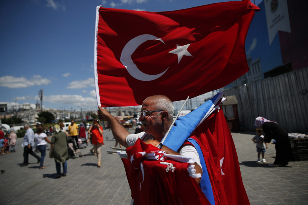 A vendor offers Turkish flags for sale at a market in Istanbul, Monday, Aug. 13, 2018. Turkey's central bank announced a series of measures on Monday to free up cash for banks as the country grapples with a currency crisis sparked by concerns over President Recep Tayyip Erdogan's economic policies and a trade and diplomatic dispute with the United States. (Lefteris Pitarakis/AP)