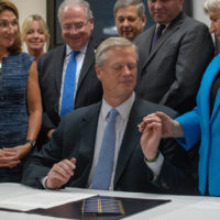 Gov. Charlie Baker handed a ceremonial pen to state Rep. Denise Garlick, co-chairwoman of the Mental Health, Substance Use and Recovery Committee. (Chris Triunfo/SHNS)