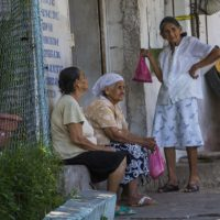 Three women wait outside of the Iglesia Profetica Esposa del Cordero la Central in San Salvador. (Jesse Costa/WBUR)