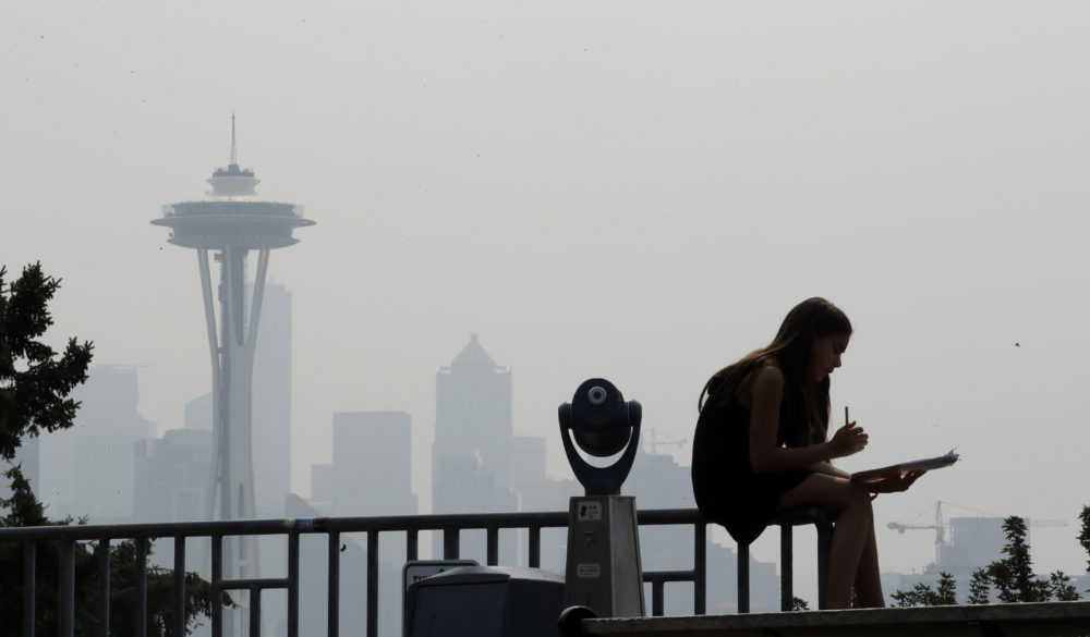 A girl works on a drawing next to an unused viewing scope as a smoky haze obscures the Space Needle and downtown Seattle behind, Tuesday, Aug. 14, 2018. Public-health officials are warning of unhealthy air across parts of the Pacific Northwest as smoke from wildfires move across the region. (Elaine Thompson/AP)