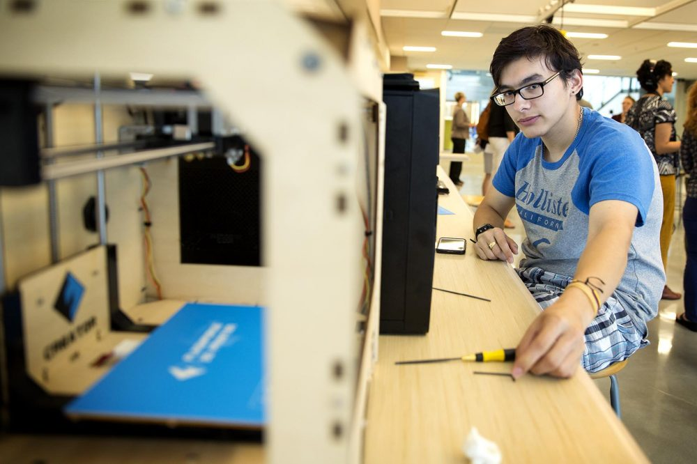 Dearborn STEM Academy student Elias Arroyave checks the functioning of a 3D printer in the school's Fab Lab maker space. (Robin Lubbock/WBUR)