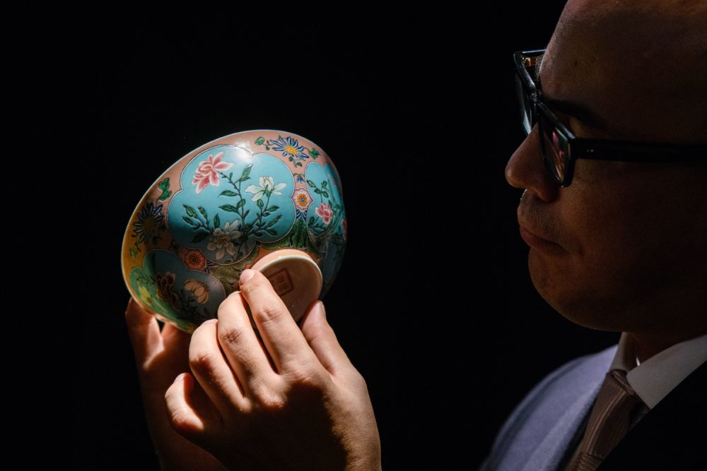 Nicolas Chow, deputy chairman for Sotheby's Asia, holds an extremely rare Qing Dynasty bowl during a media preview at auction house Sotheby's in Hong Kong on March 1, 2018. (Anthony Wallace/AFP/Getty Images)