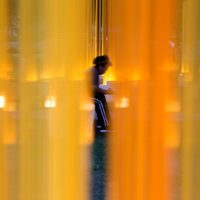 "A visitor sits in one of the inner circles of Teresita Fernández's ""Autumn (…Nothing Personal)."" (Robin Lubbock/WBUR)"