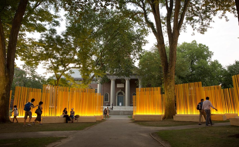 "Visitors to Harvard Yard pass through the middle of Teresita Fernández's ""Autumn (…Nothing Personal),"" as the installation lights up the leaves on the trees around it in the early evening. (Robin Lubbock/WBUR)"