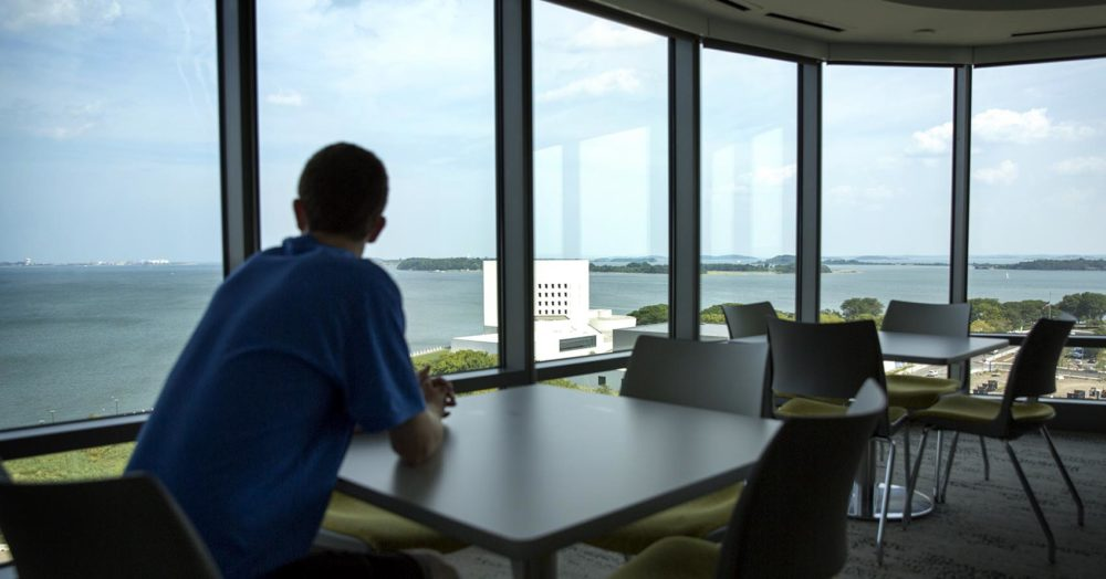 Eriq Gassé looks out over the Harbor Islands from a 12th-floor common room at UMass' new Residence Hall. (Robin Lubbock/WBUR)