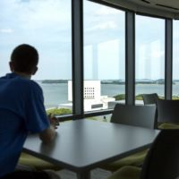 Eriq Gassé looks out over the Harbor Islands from a common room at UMass' new Residence Hall. (Robin Lubbock/WBUR)