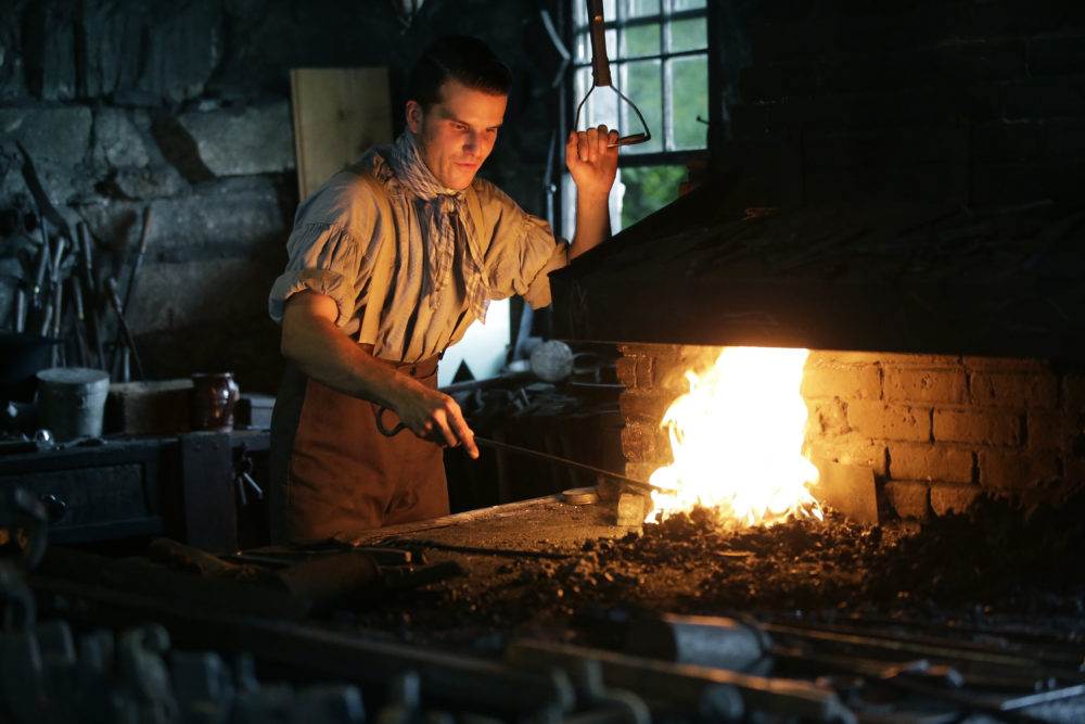 Derek Heidemann reenacts an 1830s blacksmith at Old Sturbridge Village. (Steven Senne/AP)
