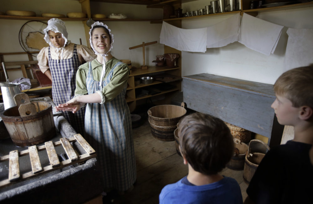 Hannah Ingersoll, left, and Loralei Arndt, second from left, reenact 1830s farm workers as children look on in a cheese room at Old Sturbridge Village. (Steven Senne/AP)