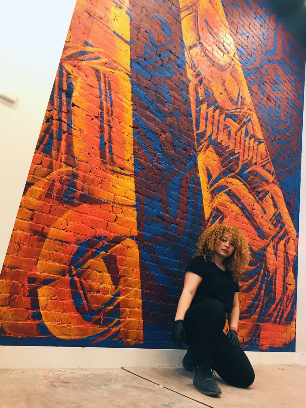 Artist Sneha Shrestha in front of one of her murals. (Courtesy of the artist)