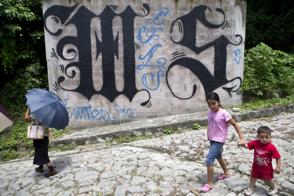 In this Aug. 21, 2014 file photo, a family walks by a wall covered by a symbol from the Mara Salvatrucha, of MS-13 gang in Ilopango, El Salvador. (Esteban Felix/AP)