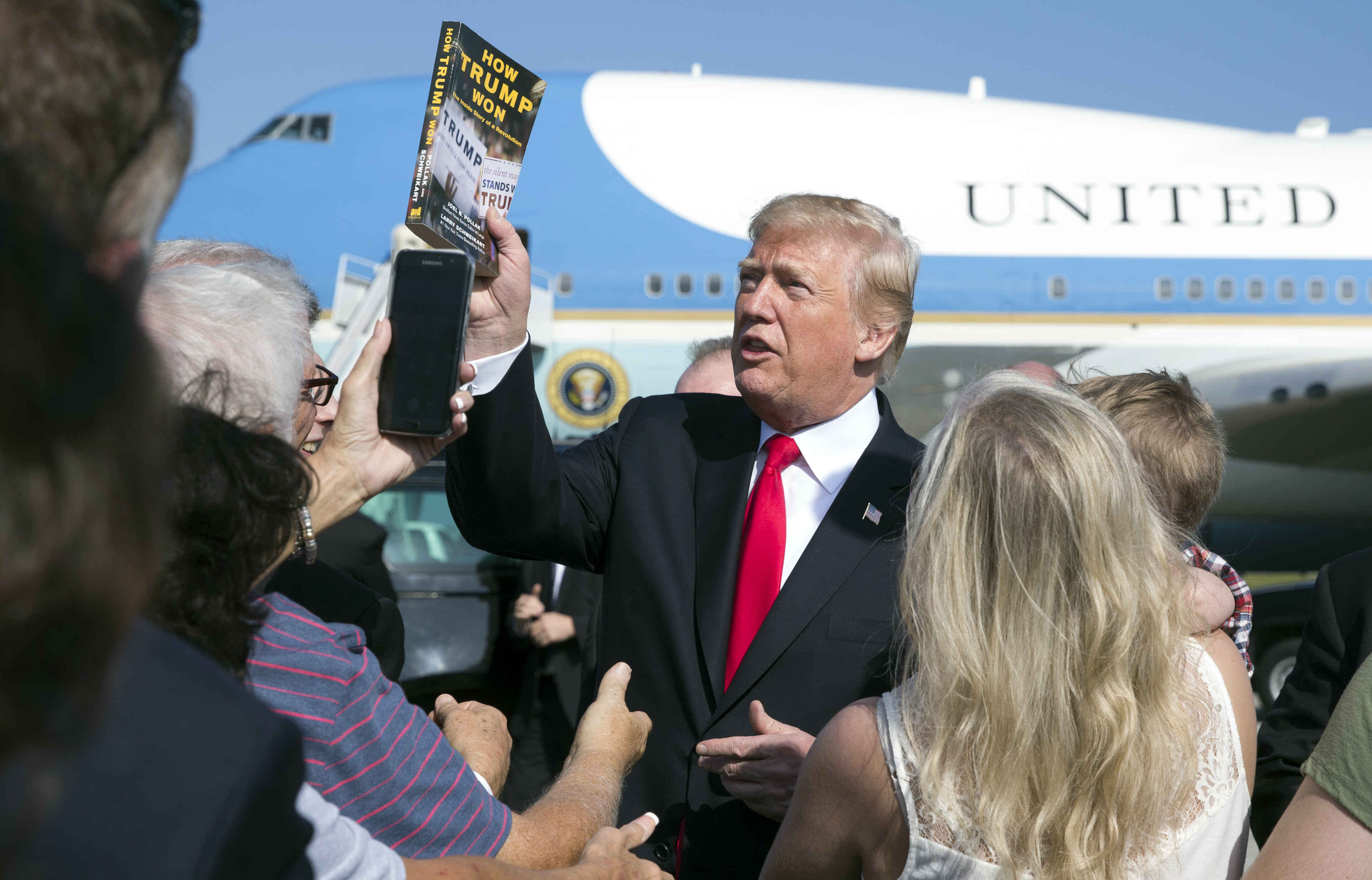 """President Donald Trump holds up the book """"How Trump Won The Inside Story of a Revolution"""" as he greets people on the tarmac as he arrives on Air Force One at Palm Beach International Airport, in West Palm Beach, Fla., Friday, Dec. 22, 2017. (Carolyn Kaster/AP)"""